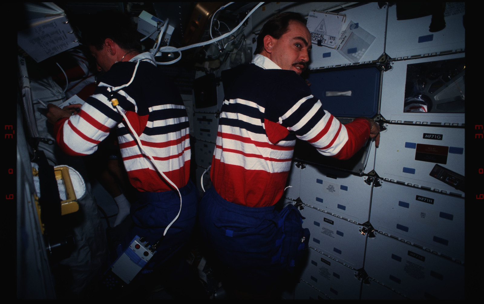 STS044-16-035 - STS-044 - STS-44 Pilot Henricks and PS Hennen work on OV-104's middeck