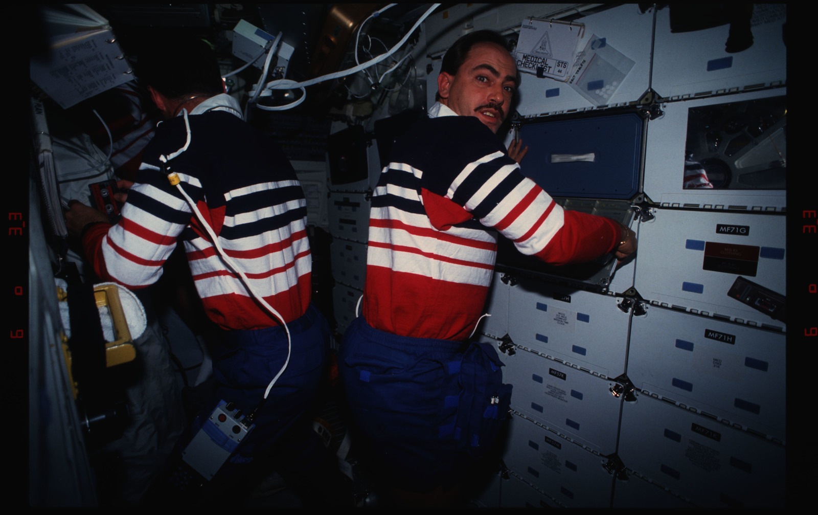 STS044-16-036 - STS-044 - STS-44 Pilot Henricks and PS Hennen work on OV-104's middeck