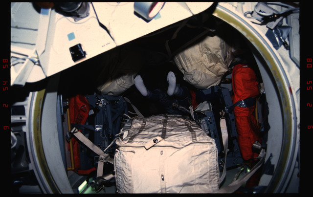 STS050-03-003 - STS-050 - Legs and feet of an unidentified male crewmember transiting the airlock.