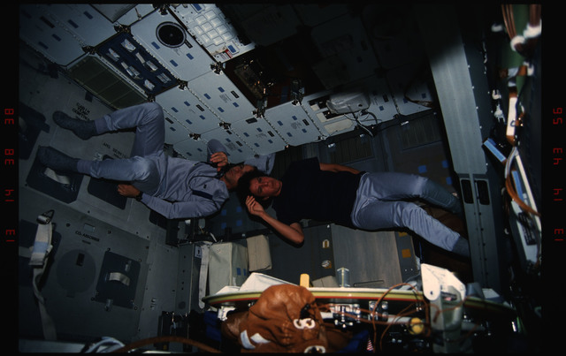 STS050-10-032 - STS-050 - Mission Specialists Ellen Baker and Carl Meade at leisure in the mid deck.