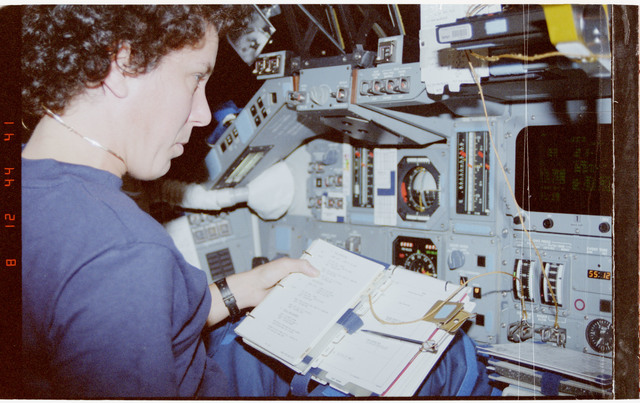 STS050-273-037 - STS-050 - Crewmember on the forward flight deck reviewing a procedures document.
