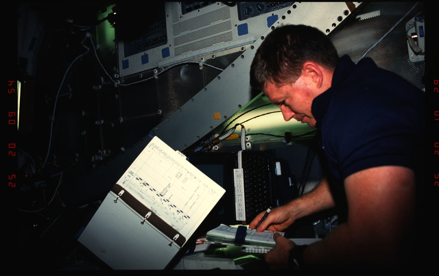 STS052-02-015 - STS-052 - Crewmember in the middeck working on an inflight experiment.