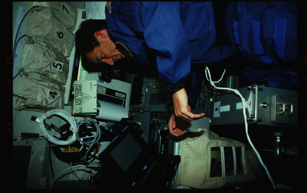 STS052-40-019 - STS-052 - Crewmember in the aft flight deck setting up the ergometer exerciser.