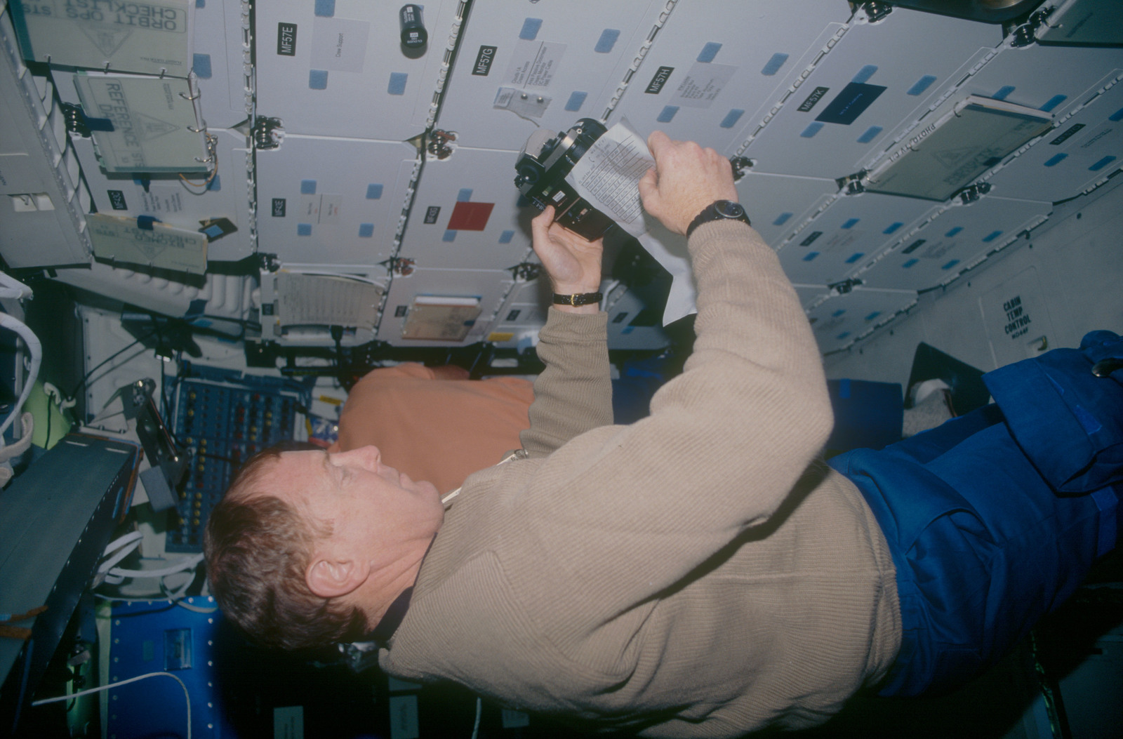STS053-06-019 - STS-053 - Crewmember in the MDDK with a 35 mm camera and operating instructions