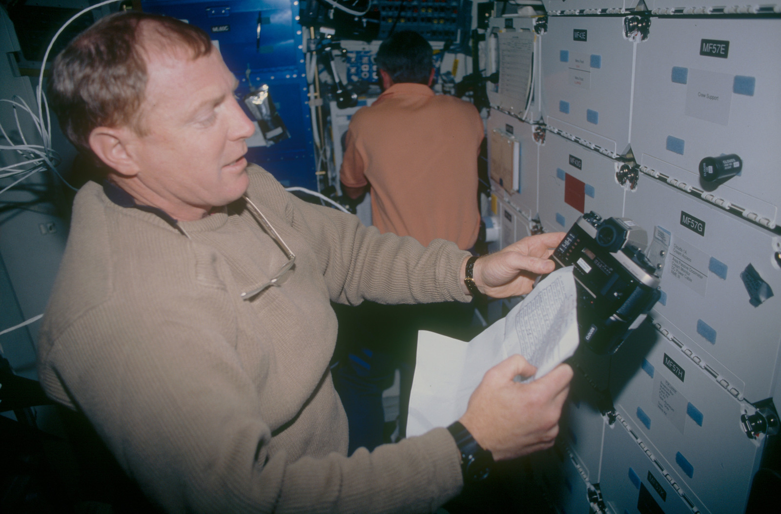 STS053-06-021 - STS-053 - Crewmember in the MDDK with a 35 mm camera and operating instructions