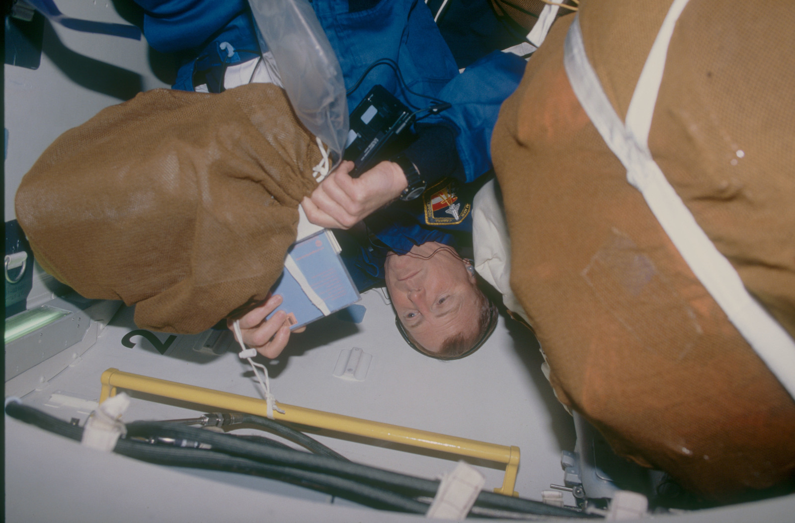 STS053-07-012 - STS-053 - Crewmember in the MDDK air lock with stowage bags