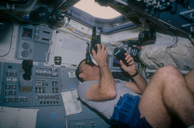 STS053-12-023 - STS-053 - Crewmember in the aft FD photographing the Earth.
