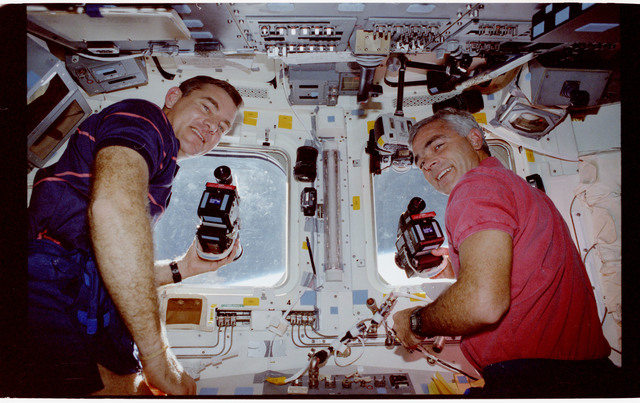 STS053-240-011 - STS-053 - Crewmembers photographing the Earth from the aft FD windows