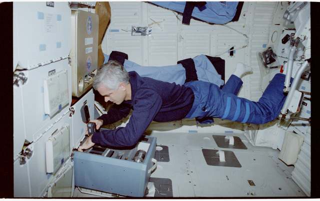 STS053-243-020 - STS-053 - Crewmember unpacking cameras from the MDDK stowage lockers