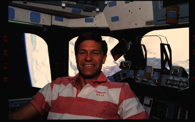 STS054-07-033 - STS-054 - Crewmember in the flight deck with views of Earth through the windows.