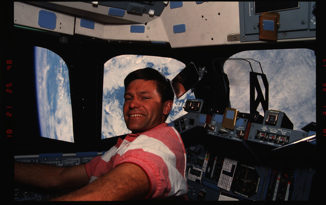 STS054-07-034 - STS-054 - Crewmember in the flight deck with views of Earth through the windows.
