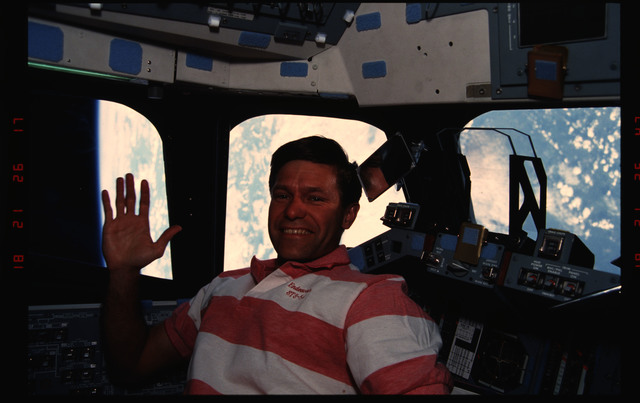 STS054-07-035 - STS-054 - Crewmember in the flight deck with views of Earth through the windows.