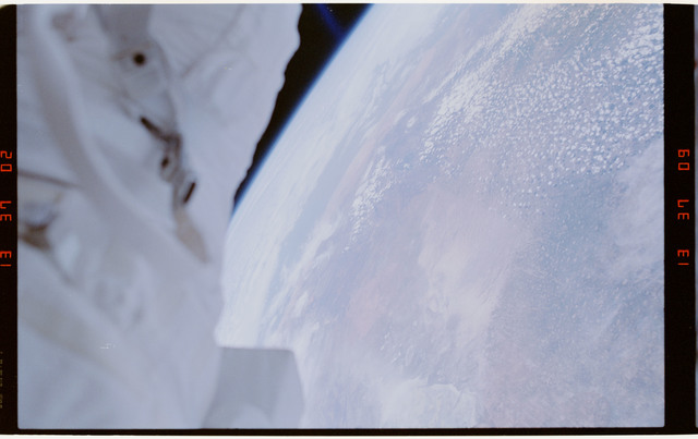 STS054-29-033 - STS-054 - EVA crewmember's legs dangling over empty space and payload bay, Earth below.