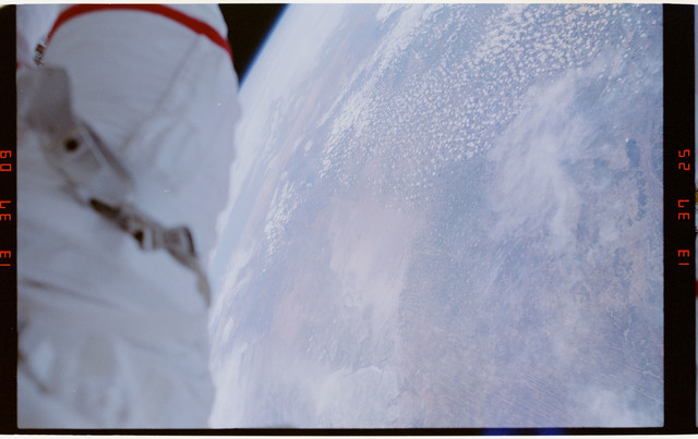 STS054-29-034 - STS-054 - EVA crewmember's legs dangling over empty space and payload bay,Earth below.