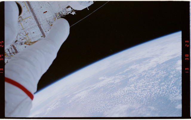 STS054-29-035 - STS-054 - EVA crewmember's legs dangling over empty space and payload bay,Earth below.