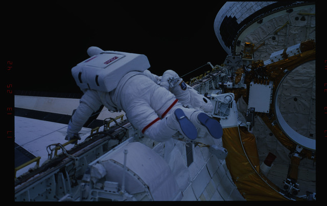 STS054-33-022 - STS-054 - Views of EVA Crewmembers working in the payload bay carrying one another.