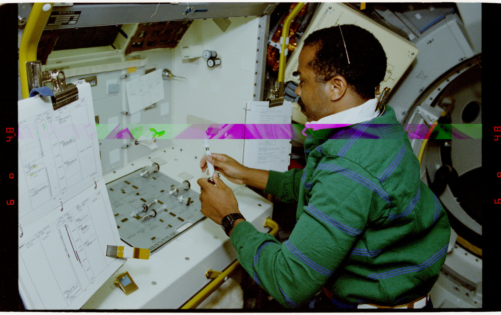 STS055-23-014 - STS-055 - Crewmember at Work Preparing Syringes in the D-2 Spacelab