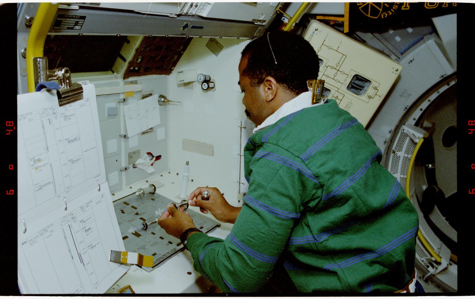 STS055-23-015 - STS-055 - Crewmember at Work Preparing Syringes in the D-2 Spacelab