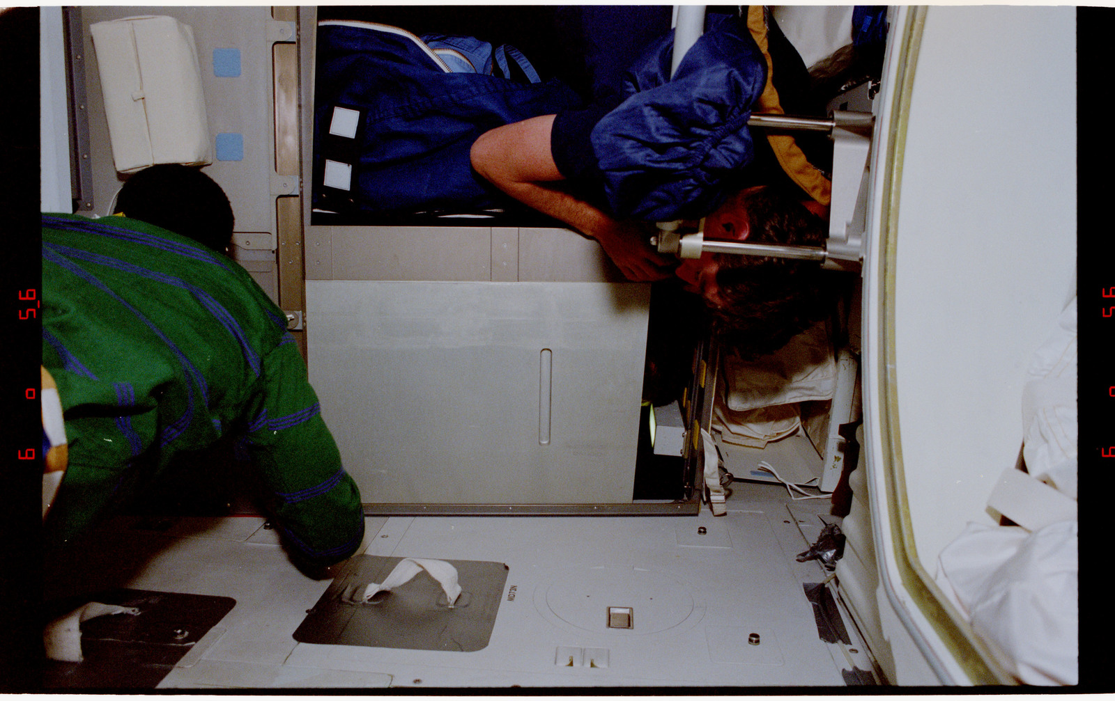 STS055-41-009 - STS-055 - Crewmembers in the middeck at the starboard sleep stations.