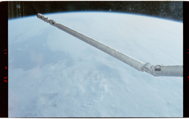 STS056-12-018 - STS-056 - Earth limb, remote manipulator system (RMS) and clouds - location unknown.