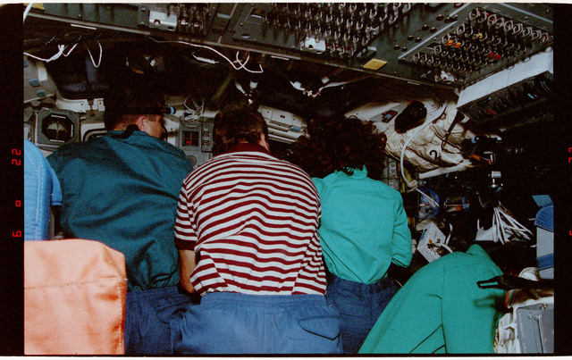 STS056-13-034 - STS-056 - Crewmembers clustered at the aft flight deck payload bay windows.