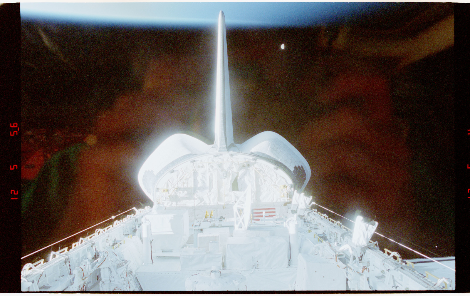 STS056-28-014 - STS-056 - Views of the payload bay, Earth limb with day/night terminator, and moon.