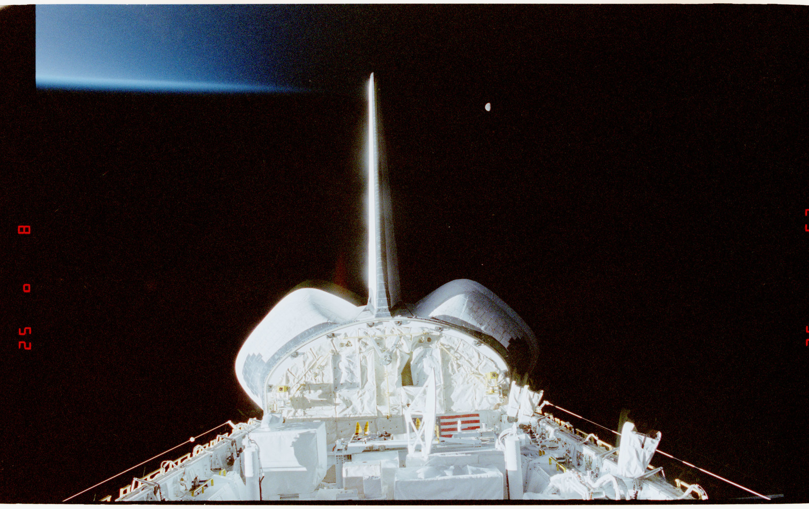 STS056-28-021 - STS-056 - Views of the payload bay, Earth limb with day/night terminator, and moon.