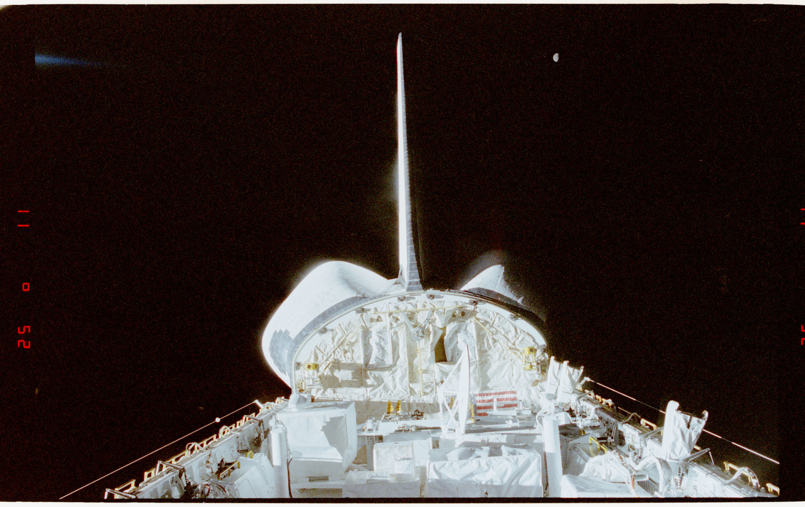 STS056-28-035 - STS-056 - Views of the payload bay, Earth limb with day/night terminator, and moon.