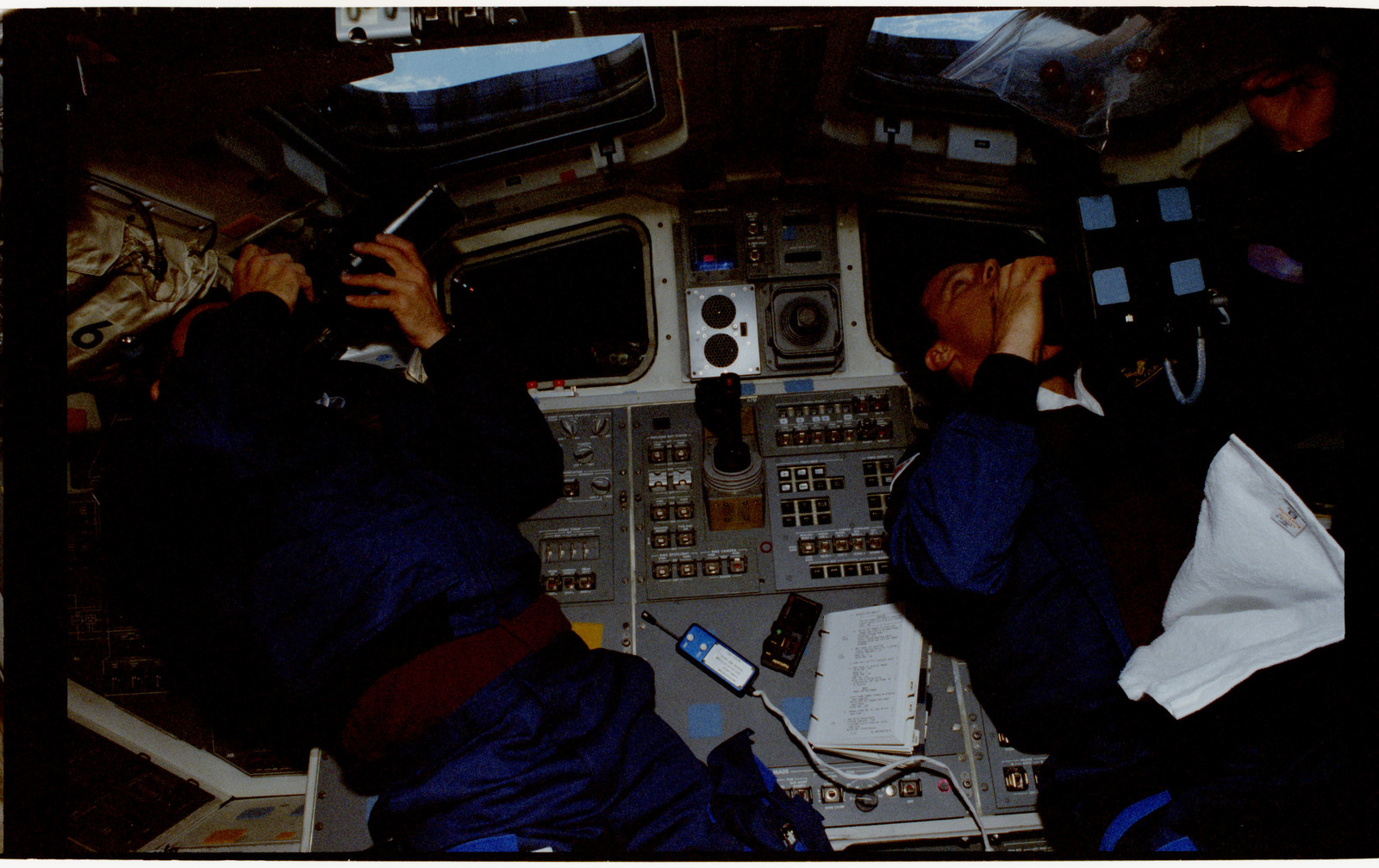 STS056-34-017 - STS-056 - Crewmembers in the aft flight deck photographing the Earth.