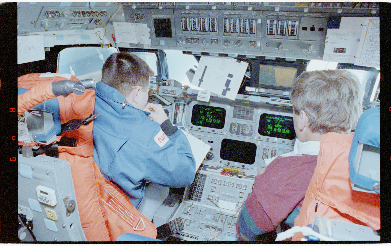 STS056-39-009 - STS-056 - Crewmembers in the fwd flight deck reviewing inflight procedures manual.