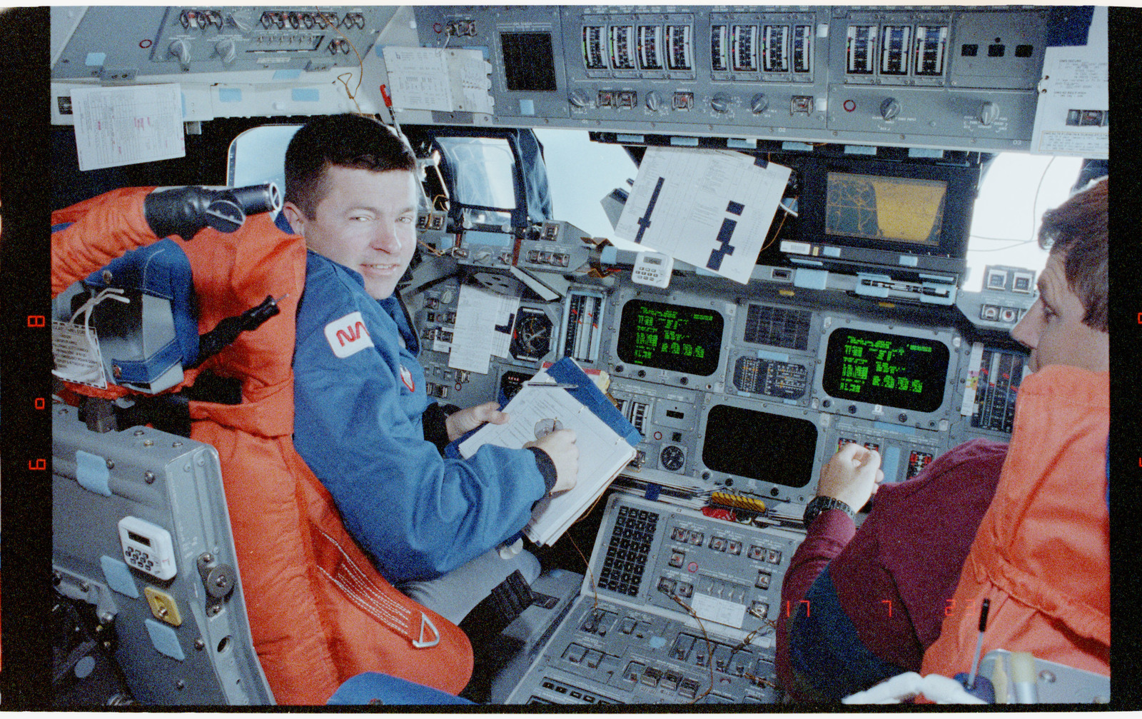 STS056-39-010 - STS-056 - Crewmembers in the fwd flight deck reviewing inflight procedures manual.