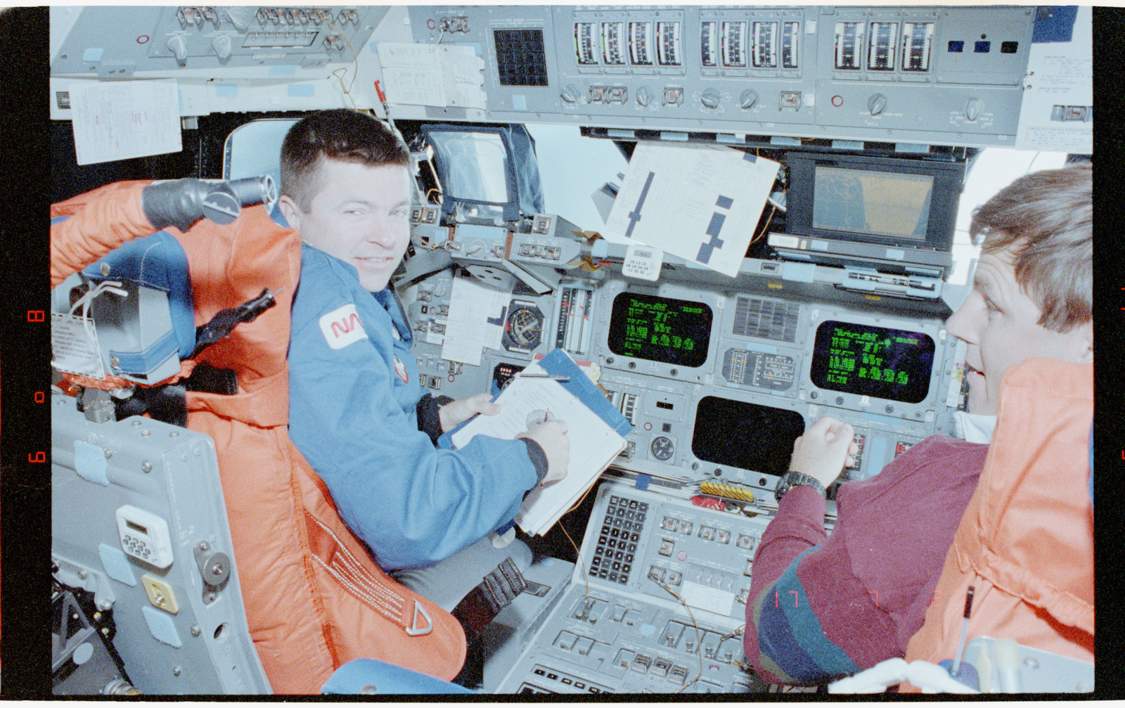 STS056-39-012 - STS-056 - Crewmembers in the fwd flight deck reviewing inflight procedures manual.