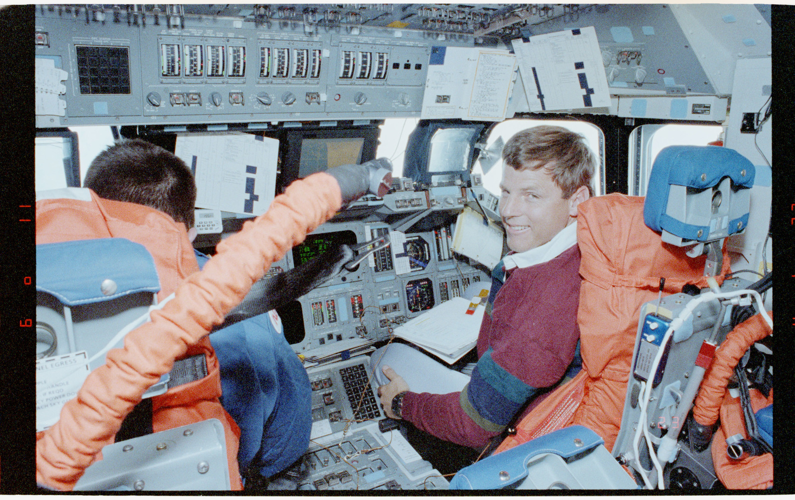 STS056-39-015 - STS-056 - Crewmembers in the fwd flight deck reviewing inflight procedures manual.
