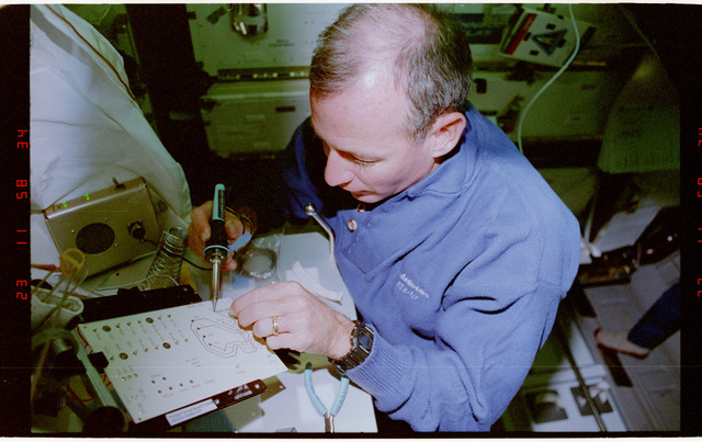 STS057-231-010 - STS-057 - Crewmember in the SPACEHAB at work on physical stability and dexterity exp.