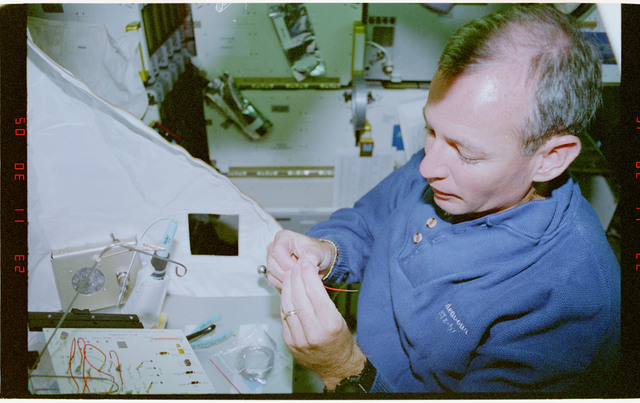 STS057-30-035 - STS-057 - Crewmember in the SPACEHAB at work on physical stability and dexterity exp.
