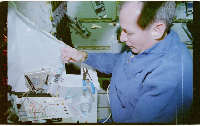 STS057-30-038 - STS-057 - Crewmember in the SPACEHAB at work on physical stability and dexterity exp.