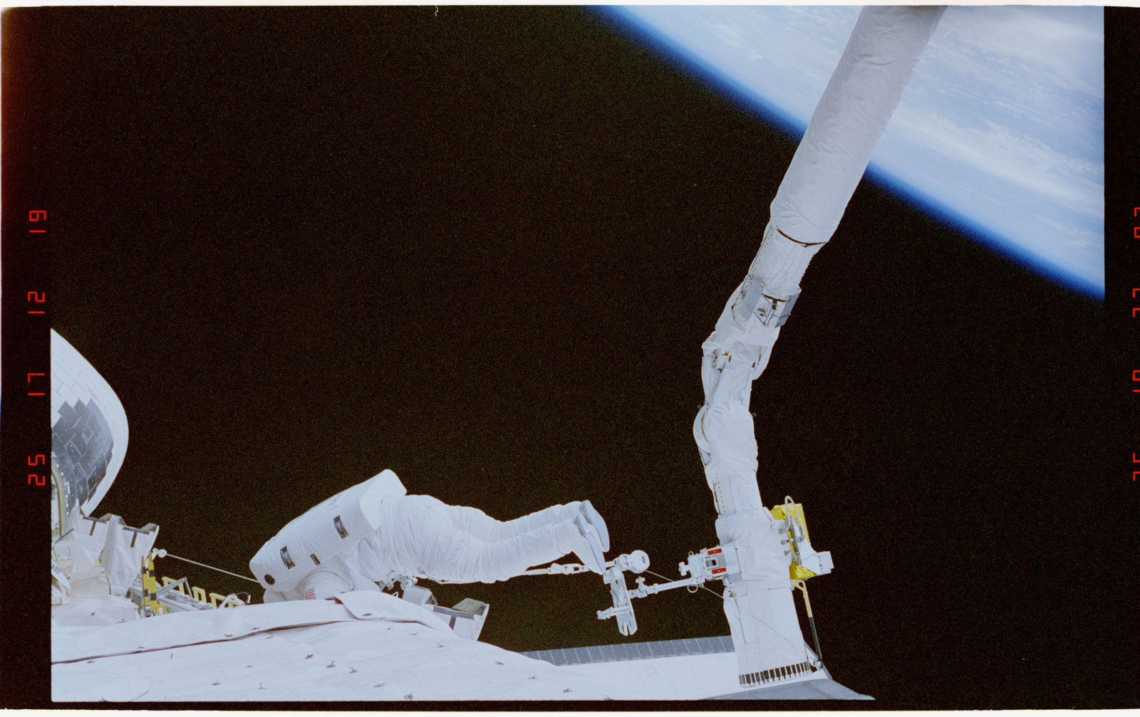 STS057-32-012 - STS-057 - EVA crewmembers with the RMS, working in the aft payload bay.
