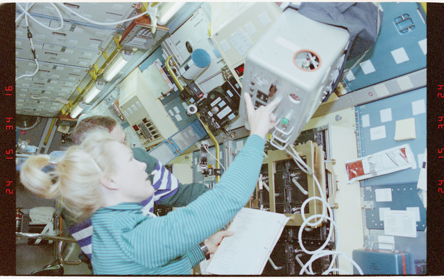 STS058-204-006 - STS-058 - Crewmembers in the SPACELAB setting up the exerciser expelled gas analyzer.
