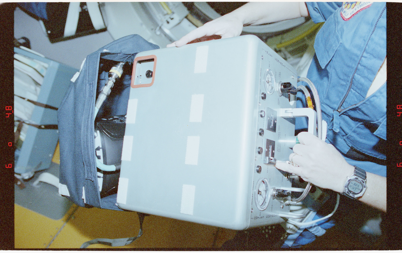 STS058-210-034 - STS-058 - Crewmembers in the SPACELAB setting up the exerciser expelled gas analyzer.