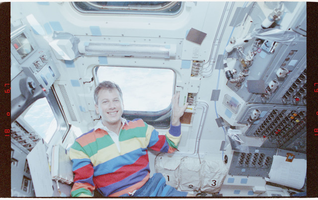STS058-212-018 - STS-058 - Candid views of a crewmember in the aft flight deck by the overhead windows.
