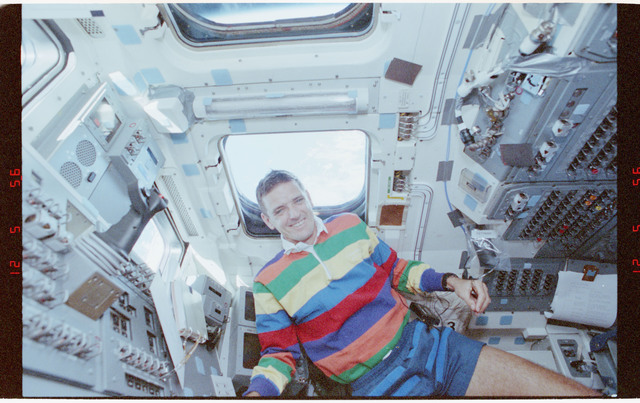 STS058-212-021 - STS-058 - Candid views of a crewmember in the aft flight deck by the overhead windows.