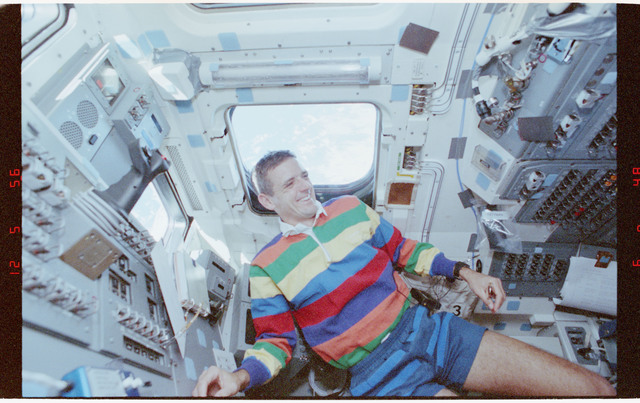 STS058-212-022 - STS-058 - Candid views of a crewmember in the aft flight deck by the overhead windows.