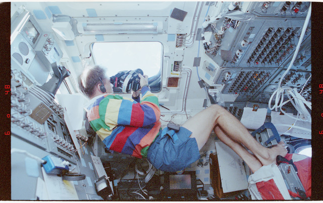 STS058-212-024 - STS-058 - Crewmember in aft flight deck overhead windows photographing Earth features.
