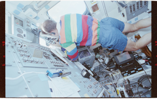 STS058-212-026 - STS-058 - Crewmember in aft flight deck overhead windows photographing Earth features.