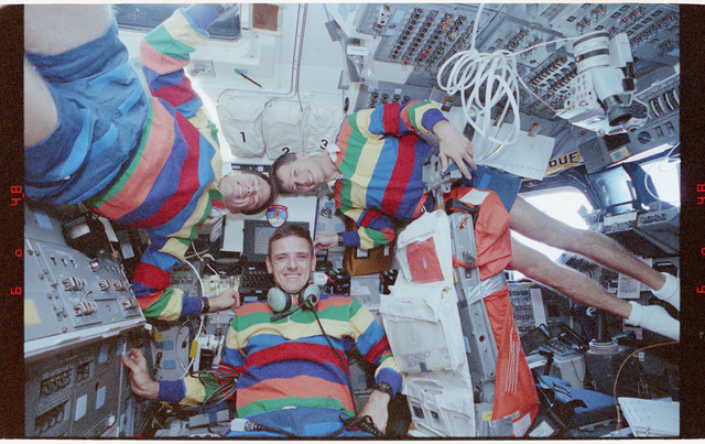 STS058-212-027 - STS-058 - Candid views of thre crewmembers in the aft flight deck at the Payloads Station.
