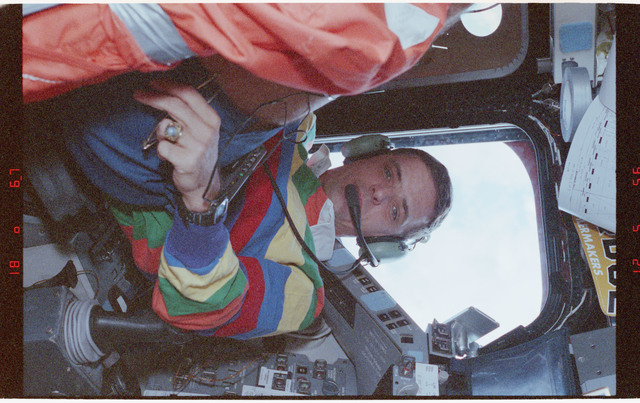 STS058-212-029 - STS-058 - Candid view of a crewmember in the aft flight deck by the overhead windows.