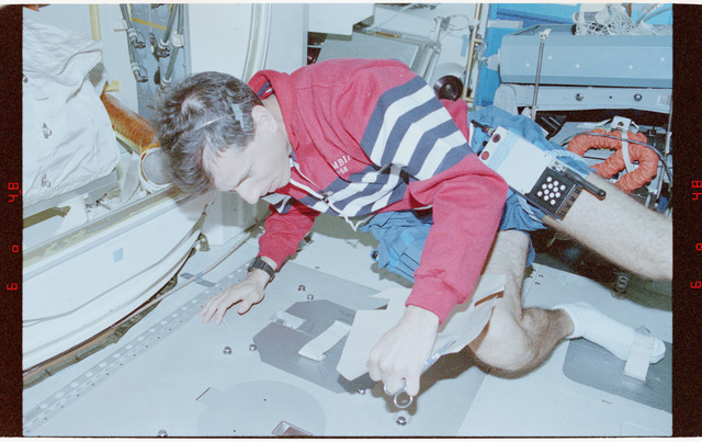 STS058-23-024 - STS-058 - Crewmember affixing an adhesive foot restraint to the middeck floor.