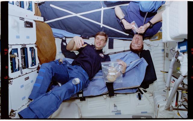 STS060-54-005 - STS-060 - Sega and Krikalev eating snacks on middeck