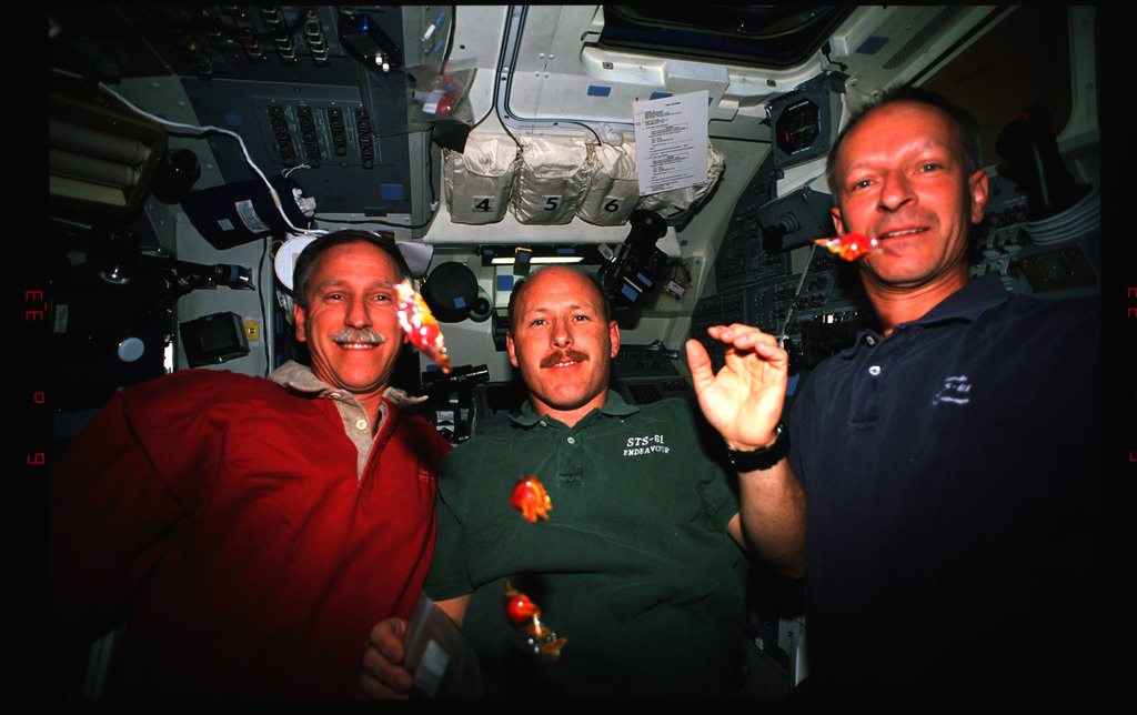 STS061-23-014 - STS-061 - Covey, Bowersox and Nicollier on middeck with candy