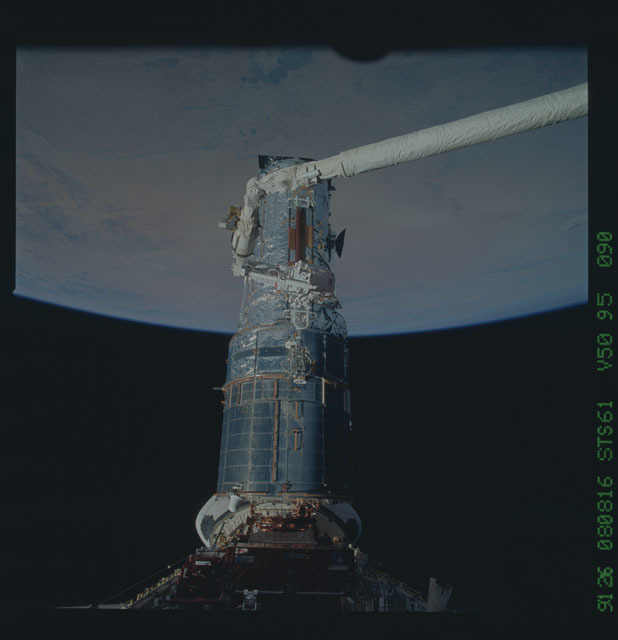 STS061-95-090 - STS-061 - Astronauts Akers and Thornton remove one of HST solar arrays during EVA
